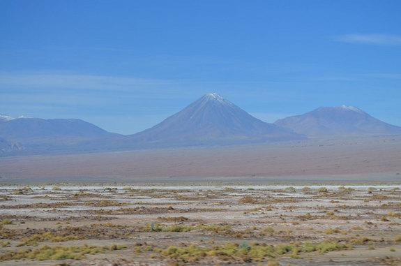 Green scrub dots the ground in some places in Chile's Atacama desert, while pointed volcanoes tower over the scene.