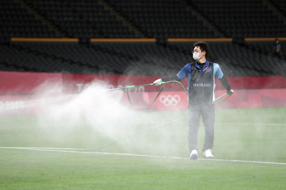 <p>An official sprays disinfectant onto the pitch in an attempt to halt the spread of the Covid-19 coronavirus ahead of the Tokyo 2020 Olympic Games men's group C first round football match between Argentina and Australia at the Sapporo Dome in Sapporo on July 22, 2021. (Photo by ASANO IKKO / AFP) </p>