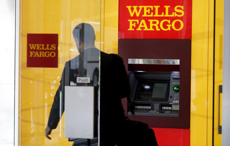 FILE PHOTO: A man walks by a bank machine at the Wells Fargo & Co. bank in downtown Denver