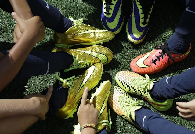 In this Thursday, Aug. 1, 2014, photo, children's shoes are shown as children take a break during a soccer camp held by FC Barcelona in Miami. European clubs like Barcelona, Liverpool and Arsenal have long sent coaches to work at U.S. summer camps, but now some are opening year-round U.S. academies aimed at finding new talent but also to expand their fan bases. This is part of a number of initiatives of major teams to grow their brands in the U.S. (AP Photo/Lynne Sladky)