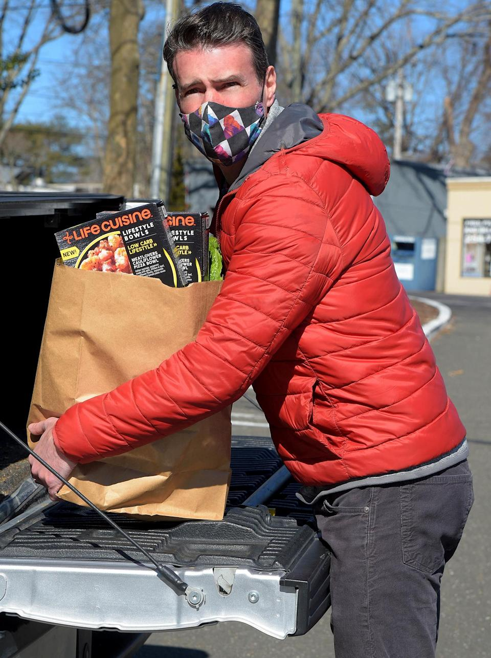 <p>Scott Foley grabs some Life Cuisine meals during a Wednesday grocery run in Connecticut. </p>