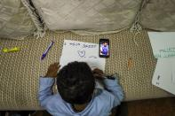 Son of Reuters cameraman Kumerra Gemechu writes a letter to his father whose picture is seen on a cell phone screen, in Addis Ababa