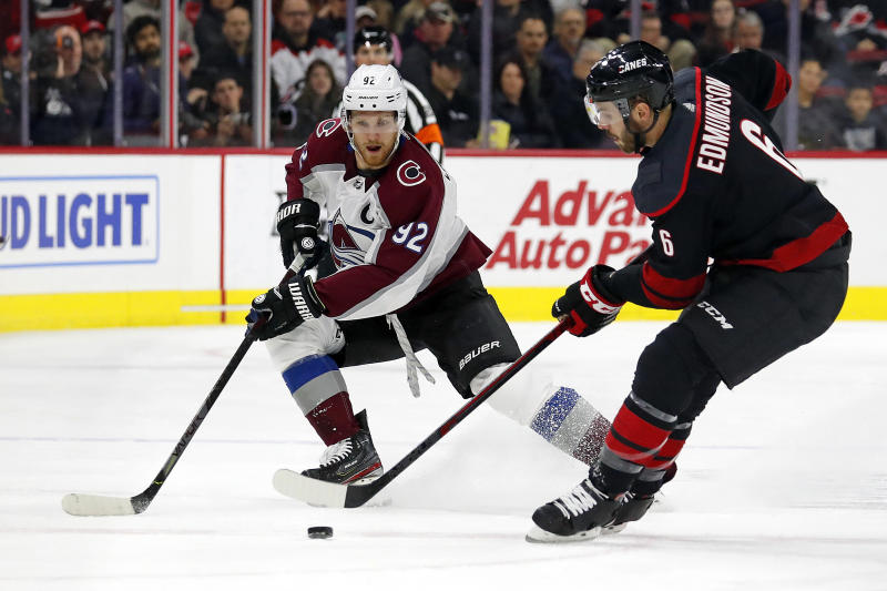 Carolina Hurricanes' Joel Edmundson (6) tries to clear the puck past Colorado Avalanche's Gabriel Landeskog (92), of Sweden, during the first period of an NHL hockey game in Raleigh, N.C., Friday, Feb. 28, 2020. (AP Photo/Karl B DeBlaker)