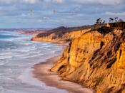 """<p><strong>Give us the wide-angle view: what kind of beach are we talking about?</strong> A sandy, two-mile strip of sand flanked by dramatic bluffs and some of the most serious swells in Southern California. (Beginners, you've been warned.) Surf aside, Black's is also a nude beach where some people do still sunbathe in their birthday suits.</p> <p><strong>How accessible is it?</strong> The most common access point—from the Torrey Pines Gliderport where you can park for free in their dirt lot—is also the most precarious. It involves trekking down a steep trail of concrete, sand, and steps. If the tide is low, you can walk over from <a href=""""https://www.cntraveler.com/activities/san-diego/la-jolla-shores?mbid=synd_yahoo_rss"""" rel=""""nofollow noopener"""" target=""""_blank"""" data-ylk=""""slk:La Jolla Shores"""" class=""""link rapid-noclick-resp"""">La Jolla Shores</a> (three miles south) or <a href=""""https://www.cntraveler.com/activities/san-diego/torrey-pines-state-natural-reserve?mbid=synd_yahoo_rss"""" rel=""""nofollow noopener"""" target=""""_blank"""" data-ylk=""""slk:Torrey Pines State Beach"""" class=""""link rapid-noclick-resp"""">Torrey Pines State Beach</a> (two miles north) instead.</p> <p><strong>Decent services and facilities, would you say?</strong> It's a BYO situation—blankets, towels, umbrellas, toys, you name it.</p> <p><strong>How's the actual beach stuff—sand and surf?</strong> If you pray for surf, you'll be rewarded with epic swells, particularly in the winter. Otherwise, we suggest laying out on the sand and enjoying the dramatic landscape. With bluffs this tall, it feels like it's just you, the ocean, the other beachgoers, and the occasional paraglider.</p> <p><strong>Can we go barefoot?</strong> Yes.</p> <p><strong>If we're thinking about going, what—and who—is this beach best for?</strong> If seeing sun worshippers in the buff isn't your thing, you might want to head to the more G-rated La Jolla Shores, just three miles south of Black's. </p> <p>But since access here is trickier than most Sa"""