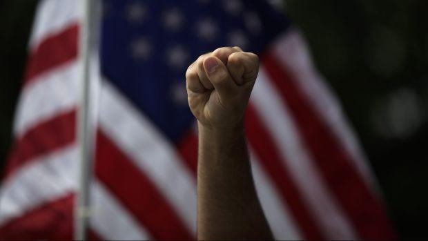 a protestor raises their fist against the american flag