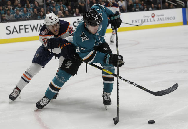 San Jose Sharks right wing Joonas Donskoi (27), from Finland, tries to get the puck in front of Edmonton Oilers defenseman Caleb Jones (82) during the first period of an NHL hockey game in San Jose, Calif., Tuesday, Jan. 8, 2019. (AP Photo/Jeff Chiu)