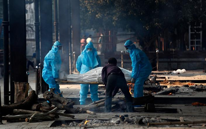 Health workers in personal protective equipment carry the body of a Covid-19 victim for cremation in New Delhi - AP