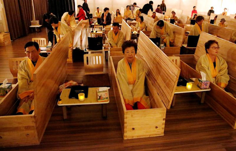 """Participants sit inside coffins during a """"living funeral"""" event as part of a """"dying well"""" programme, in Seoul, South Korea, October 31, 2019. Picture taken on October 31, 2019. REUTERS/Heo Ran TPX IMAGES OF THE DAY"""