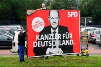 Workers remove election campaign posters after general election in Germany