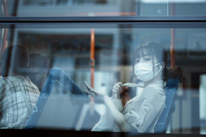 FILE - In this July 22, 2021, file photo, a woman sits on a bus ahead of the 2020 Tokyo Olympics in Mishima, Japan. (AP Photo/Thibault Camus, File)