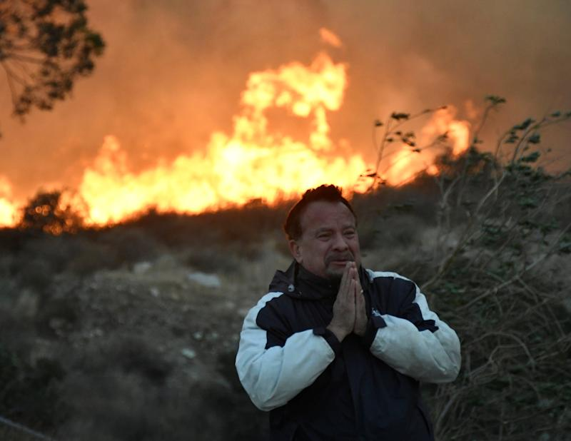 A man prays as the Creek fire advances behind him in the San Fernando Valley area of Los Angeles.