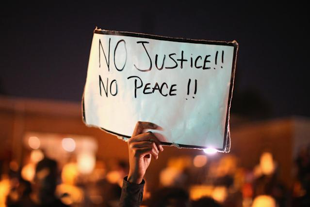 <p>Demonstrators protest the killing of teenager Michael Brown on August 12, 2014 in Ferguson, Missouri. Brown was shot and killed by a police officer on Saturday in the St. Louis suburb of Ferguson. Ferguson has experienced two days of violent protests since the killing but, tonight's protest was peaceful. (Scott Olson/Getty Images) </p>