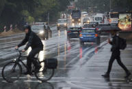 A cyclist and a passer-by with an umbrella cross a traffic light intersection during rainfall in Hamburg, Germany, Monday, June 21, 2021. (Georg Wendt/dpa via AP)
