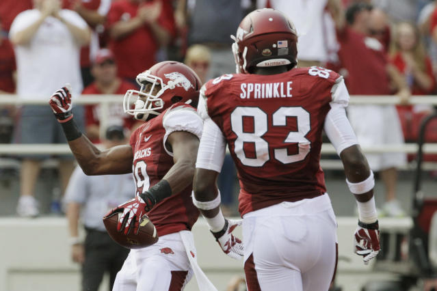 Arkansas wide receiver Javontee Herndon, left, celebrates a touchdown with tight end Jeremy Sprinkle (83) during the first half of an NCAA college football game against Louisiana-Lafayette in Fayetteville, Ark., Saturday, Aug. 31, 2013. (AP Photo/Danny Johnston)