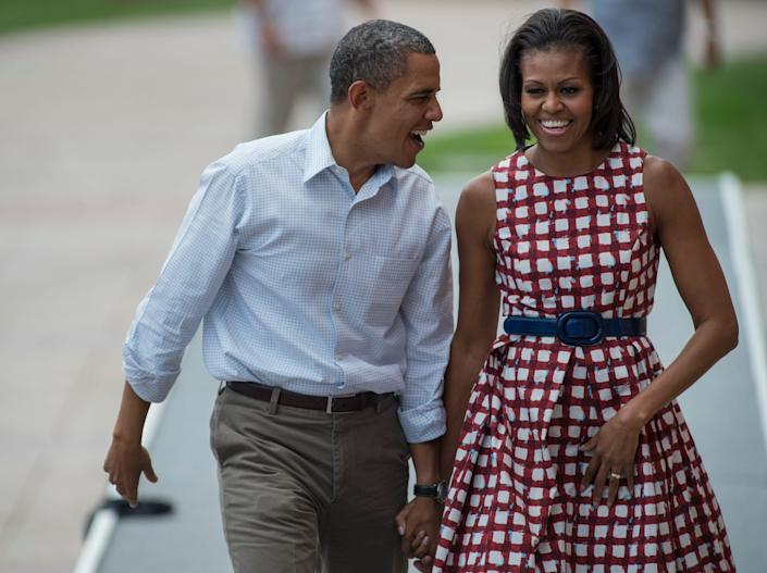 michelle and barack obama smiling at each other while campaigning in 2012