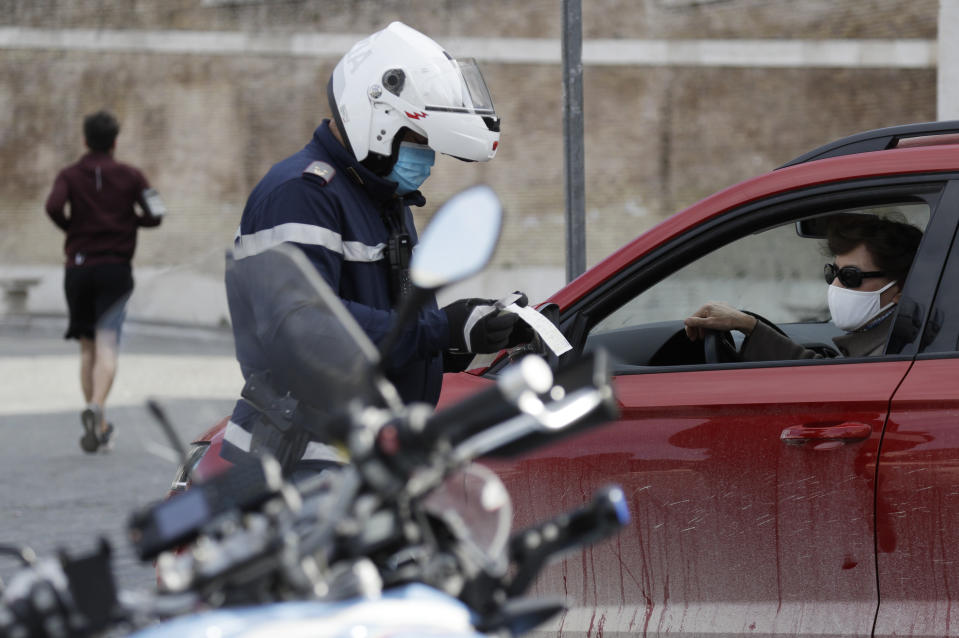 A Police officer check's a documents at a road block in Rome's central Piazza del Popolo, Saturday, April 3, 2021. Italy went into lockdown on Easter weekend in its effort to battle then Covid-19 pandemic. (AP Photo/Gregorio Borgia)