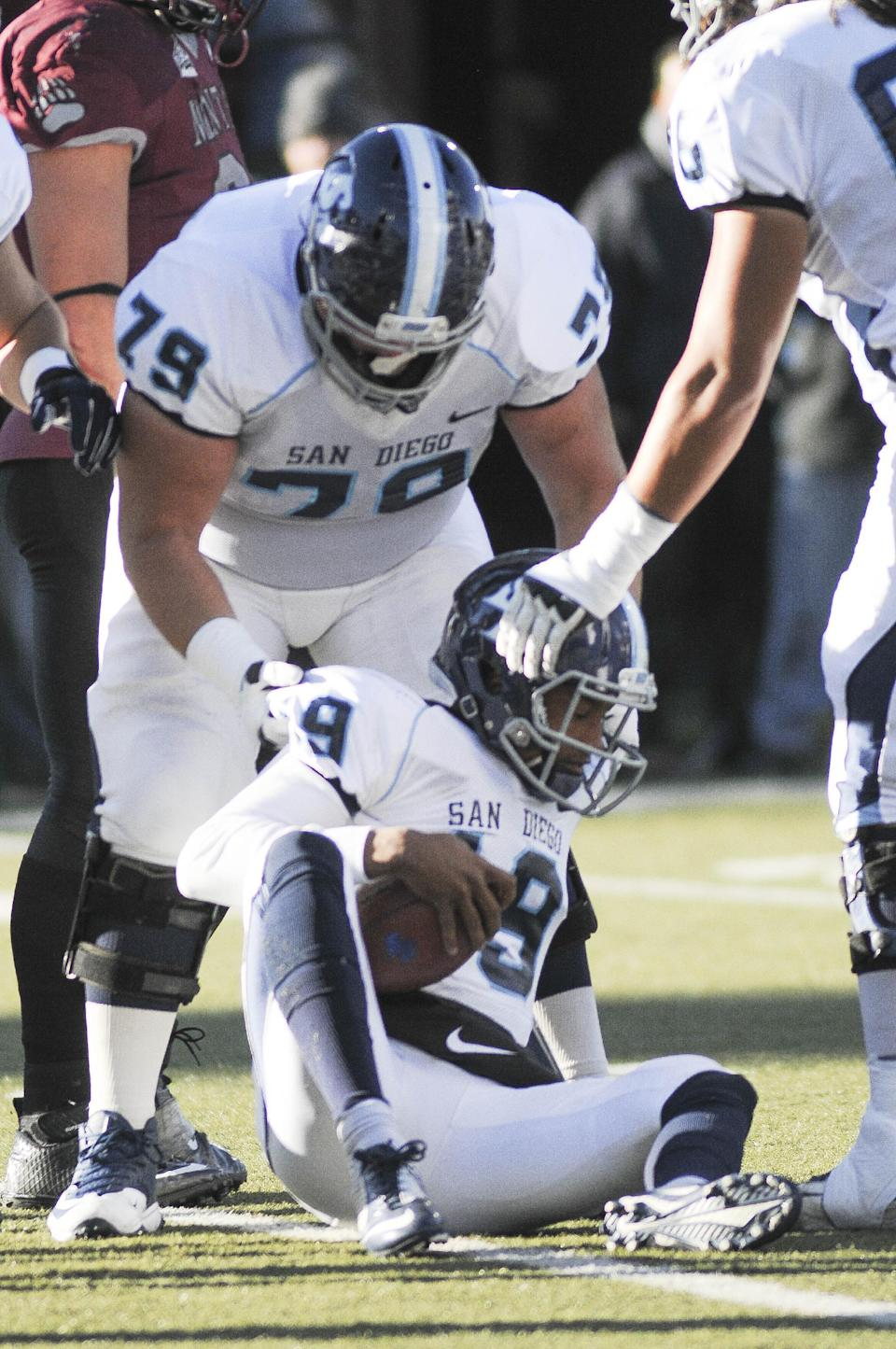 San Diego quarterback Keith Williams (19) is helped up by offensive lineman Jeff Starr (79) after being sacked during the first half of an NCAA college football playoff game against Montana, Saturday, Nov. 29, 2014, in Missoula, Mont. (AP Photo/Lido Vizzutti)