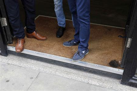 Men stand in the doorway of a barbers shop, which has a burn mark on the carpet in London September 3, 2013. REUTERS/Stefan Wermuth