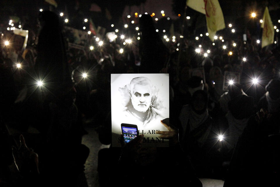A Shiite Muslim illuminates a portrait of Iranian Revolutionary Guard Gen. Qassem Soleimani, with light from a mobile phone, during a rally to condemn his killing in Iraq by a U.S. airstrike, in Karachi, Pakistan, Sunday, Jan. 5, 2020. Iran has vowed