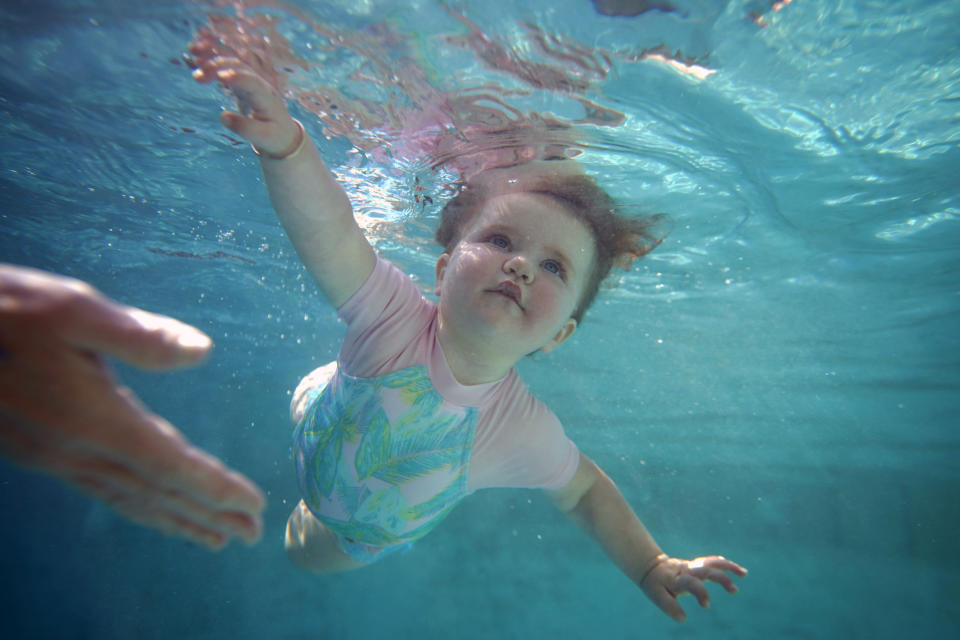 Eleven-month-old Juna Pool moves in the water during an infant survival swim class with instructor Tracey Panzer-Michelle Thursday, June 24, 2021, in Richardson, Texas. (AP Photo/LM Otero)