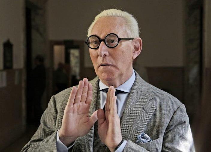 Roger Stone talks to reporters on March 30, wearing the circular, black-framed glasses for which he's known. (Photo: Seth Wenig/AP)