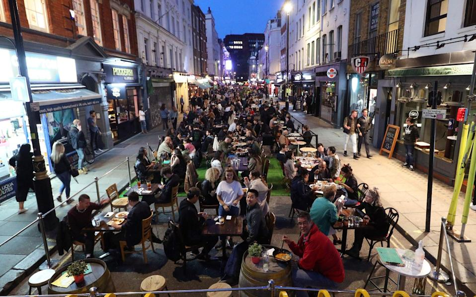 People eating on restaurant tables placed outside on Old Compton St in Soho, London, - Yui Mok/PA Wire