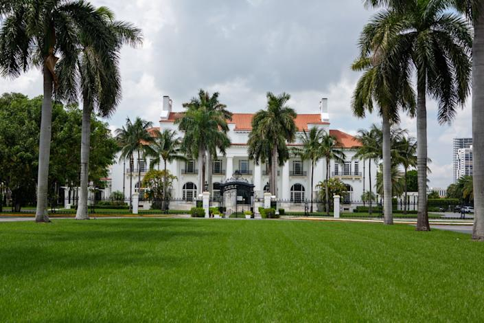 A white mansion known with a large green lawn and palm trees