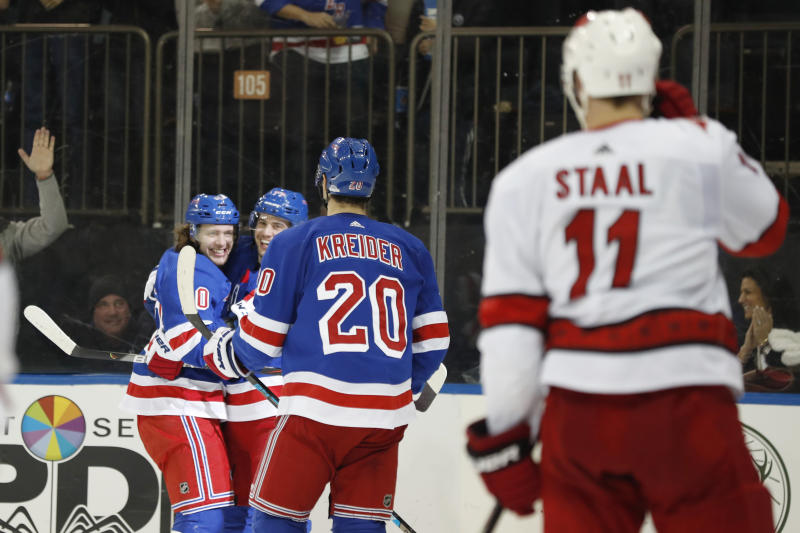 New York Rangers left wing Artemi Panarin, left, celebrates with defenseman Tony DeAngelo (77) as  left wing Chris Kreider (20) approaches them with Carolina Hurricanes center Jordan Staal (11) watching after Panarin scored a goal during the second period of an NHL hockey game Friday, Dec. 27, 2019, in New York. (AP Photo/Kathy Willens)