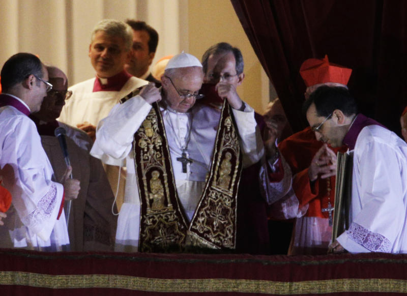 Pope Francis puts on his sash from the central balcony of St. Peter's Basilica at the Vatican, Wednesday, March 13, 2013. Cardinal Jorge Bergoglio, who chose the name of Francis is the 266th pontiff of the Roman Catholic Church. (AP Photo/Andrew Medichini)
