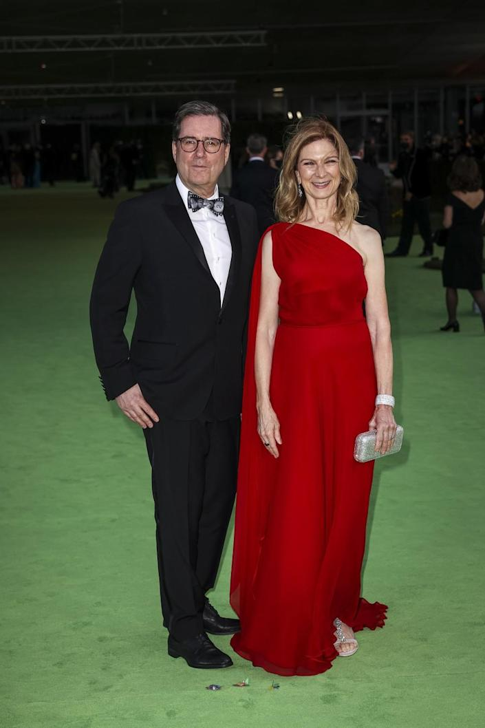 A man in a black suit and a woman in a red dress posing on a green carpet