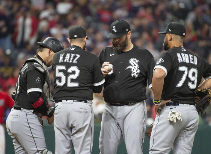 Chicago White Sox pitching coach Ethan Katz (52) has a meeting with starting pitcher Lance Lynn, center, as Yasmani Grandal, left, and Jose Abreu listen in during the sixth inning of a baseball game in Cleveland, Saturday, Sept. 25, 2021. (AP Photo/Phil Long)