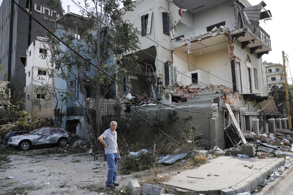 A Lebanese man stands next to his damaged house near the scene where an explosion hit on Tuesday the seaport of Beirut, Lebanon, Thursday, Aug. 6, 2020. Lebanese army bulldozers plowed through wreckage to reopen roads around Beirut's demolished port on Thursday as the government pledged to investigate the devastating explosion and placed port officials under house arrest. (AP Photo/Hussein Malla)