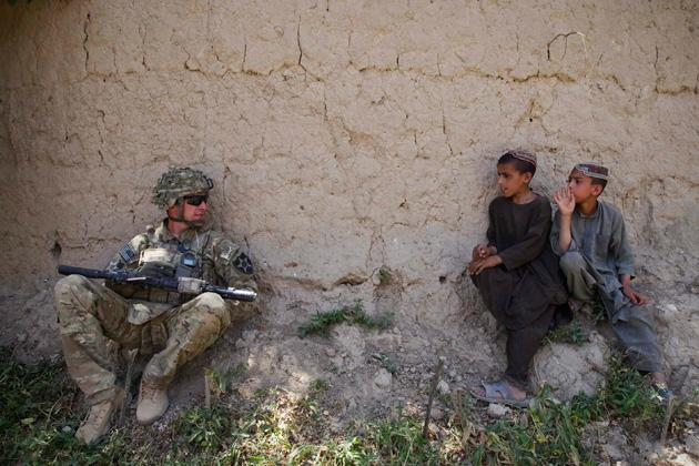 Afghan boys look at a U.S. Army soldier of 5-20 Infantry Regiment attached to the 82nd Airborne Division, in Zharay district of Kandahar province, southern Afghanistan June 10, 2012.  REUTERS/Shamil Zhumatov