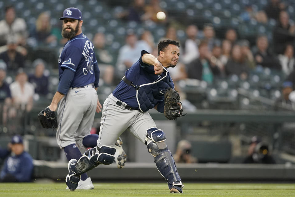 Tampa Bay Rays catcher Francisco Mejia throws out Seattle Mariners' Luis Torrens at first on a grounder as pitcher Andrew Kittredge, left, watches during the fifth inning of a baseball game Friday, June 18, 2021, in Seattle. (AP Photo/Ted S. Warren)