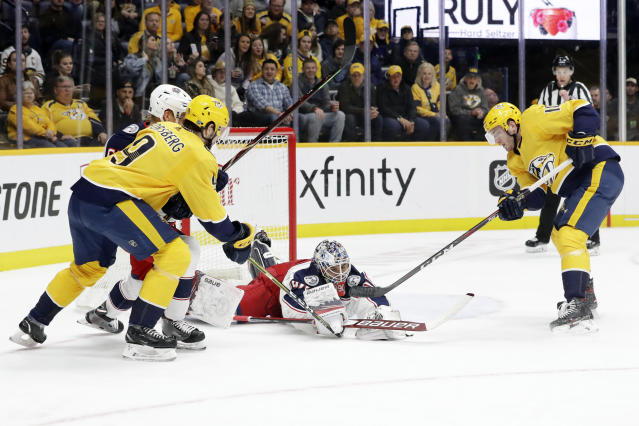 Columbus Blue Jackets goaltender Elvis Merzlikins (90) covers up the puck as Nashville Predators left wing Filip Forsberg (9), of Sweden, and center Colton Sissons (10) close in during the second period of an NHL hockey game Saturday, Feb. 22, 2020, in Nashville, Tenn. (AP Photo/Mark Humphrey)