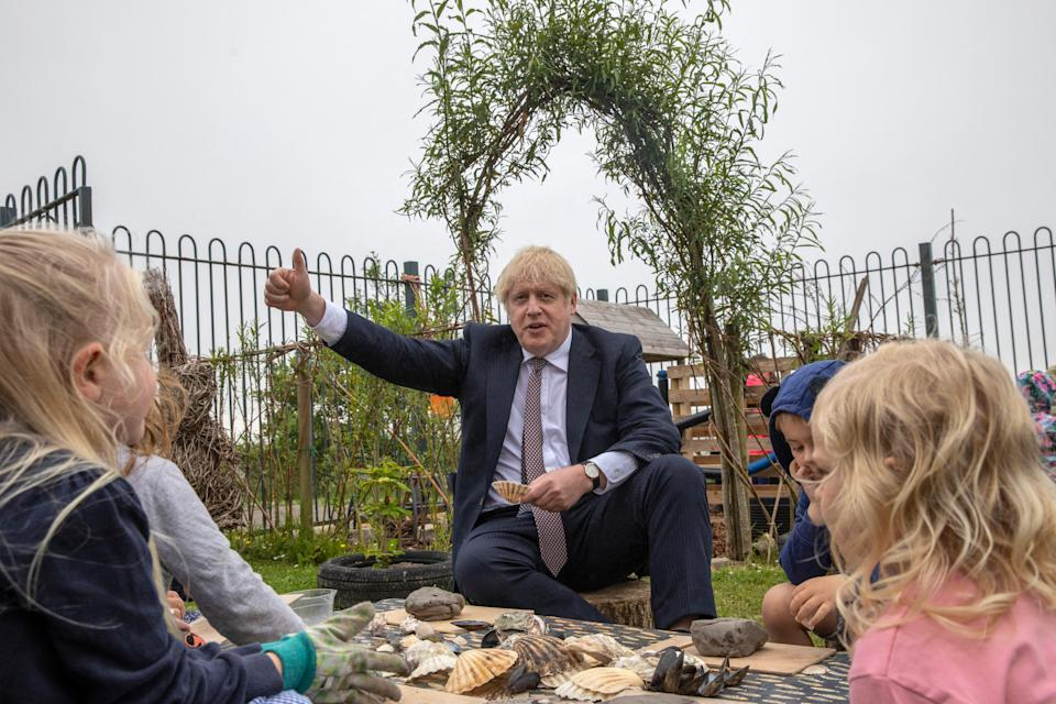 Britain's Prime Minister Boris Johnson meets children as he visits the outdoor spaces at St Issey Primary school near Wadebridge in Cornwall on June 10, 2021. (Photo by Jack Hill / POOL / AFP) (Photo by JACK HILL/POOL/AFP via Getty Images)