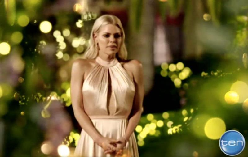 The 37-year-old blonde bomshell stuns in an off-white beige gown in what appears to be the first rose ceremony, as she awaits the arrival of her male suitors. Source: Channel Ten