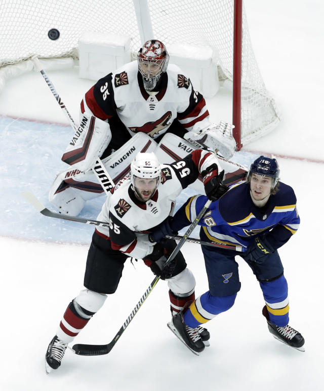 Arizona Coyotes goaltender Darcy Kuemper (35), Jason Demers (55) and St. Louis Blues' Robert Thomas (18) watch as the puck flies in the air during the first period of an NHL hockey game, Tuesday, March 12, 2019, in St. Louis. (AP Photo/Jeff Roberson)