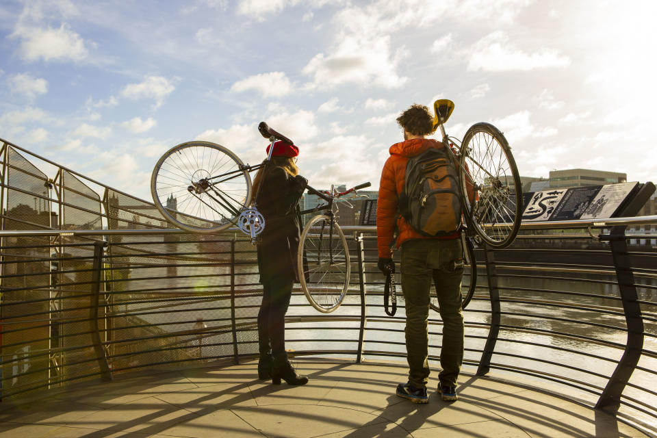 A couple carrying bicycles their shoulders by London Bridge during the Covid-19 lockdown in London. (Photo by Pietro Recchia / SOPA Images/Sipa USA)