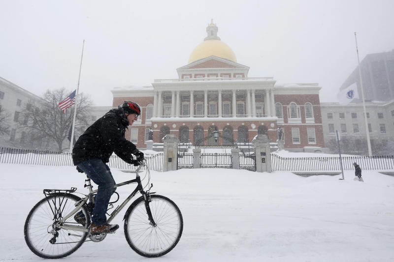 A man rides his bicycle past the State House during a blizzard in Boston, Massachusetts January 27, 2015. A blizzard swept across the northeastern United States on Tuesday, dropping more than a foot (30 cm) of snow across Massachusetts and Connecticut. REUTERS/Dominick Reuter (UNITED STATES - Tags: ENVIRONMENT)