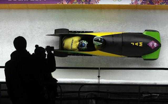 The team from Jamaica JAM-1, piloted by Winston Watts and brakeman Marvin Dixon, takes a curve on their second run during the men's two-man bobsled competition at the 2014 Winter Olympics, Sunday, Feb. 16, 2014, in Krasnaya Polyana, Russia. (AP Photo/Dita Alangkara)