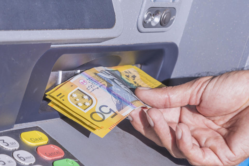 Taking several Australian $50 notes from an ATM machine
