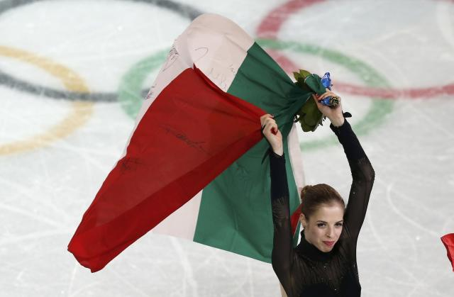 Italy's Carolina Kostner waves her national flag after placing third for the figure skating women's free skating program at the 2014 Sochi Winter Olympics, February 20, 2014. REUTERS/Issei Kato (RUSSIA - Tags: OLYMPICS SPORT FIGURE SKATING TPX IMAGES OF THE DAY)
