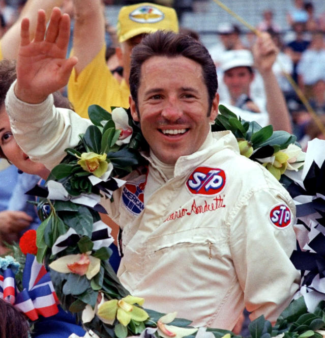 """FILE - In this May 30, 1969, file photo, Mario Andretti waves from the winner's circle after his victory in the Indianapolis 500 auto race at Indianapolis Motor Speedway in Indianapolis. Organizers announced Thursday, March 26, that the 500 would move from its traditional Memorial Day weekend slot to Aug. 23. It's a lot better than the word canceling,"""" Andretti told The Associated Press. I think the postponement is something everyone was realistically expecting and at least it's something to shoot at. To me that's encouraging, it's something we all need while we're hunkered down, staring at the ceiling. (AP Photo, File)"""