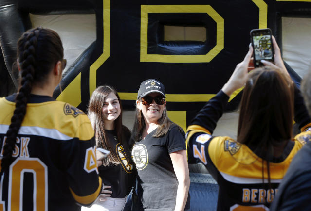 Boston Bruins fans pose for a photo outside TD Garden before Game 7 of the NHL hockey Stanley Cup Final between the Bruins and the St. Louis Blues, Wednesday, June 12, 2019, in Boston. (AP Photo/Michael Dwyer)