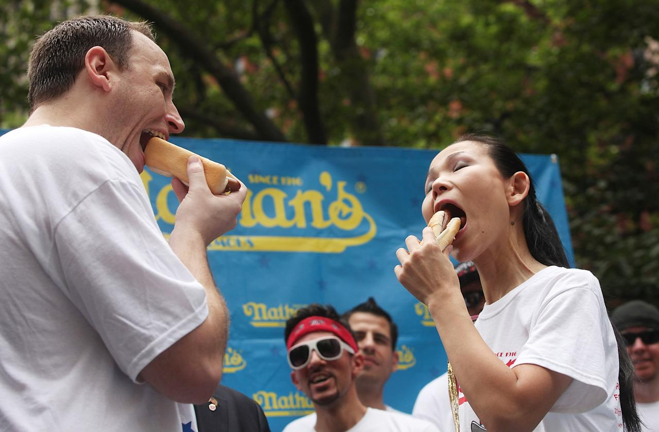 NEW YORK, NY - JULY 03: Men's world record holder Joey Chestnut (L) and women's world record holder Sonya Thomas eat a hot dog during the Nathan's Famous Fourth of July International Hot Dog Eating Contest weigh-in ceremony on July 3, 2013 in the Brooklyn borough New York City. The annual hot dog eating event is expected to draw up to 40,000 fans on July 4, in the Coney Island section of Brooklyn. (Photo by Mario Tama/Getty Images)