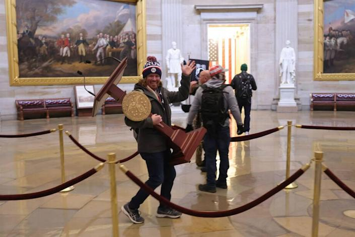 Protesters enter the U.S. Capitol Building on Jan. 6, 2021, in Washington, D.C., and one is carrying the lectern bearing the seal of the Speaker of the House. As this photo captured by chief Getty Images photographer Win McNamee quickly circulated on social media., many residents in Florida's Manatee County identified the man as Adam Christian Johnson, 36, from Parrish.