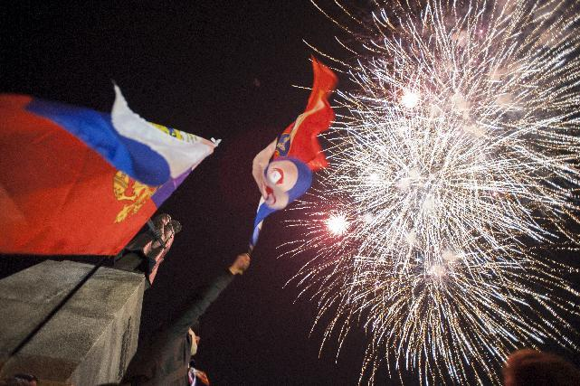 People watch fireworks at the central Nakhimov square in Sevastopol, Crimea, on Friday, March 21, 2014. Russian President Vladimir Putin completed the annexation of Crimea on Friday, signing a law making the Black Sea peninsula part of Russia. (AP Photo/Andrew Lubimov)