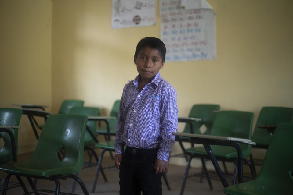 Hector Vasquez poses for a portrait inside his former classroom at the Nuevo Yibeljoj school, closed amid the new coronavirus pandemic in Chiapas state, Mexico, Friday, Sept. 11, 2020. Since schools closed in March, Vasquez is one of 12 siblings who work in the coffee fields daily instead of just the weekends, while his father helps them with school work dropped off by teachers. (AP Photo/Eduardo Verdugo)