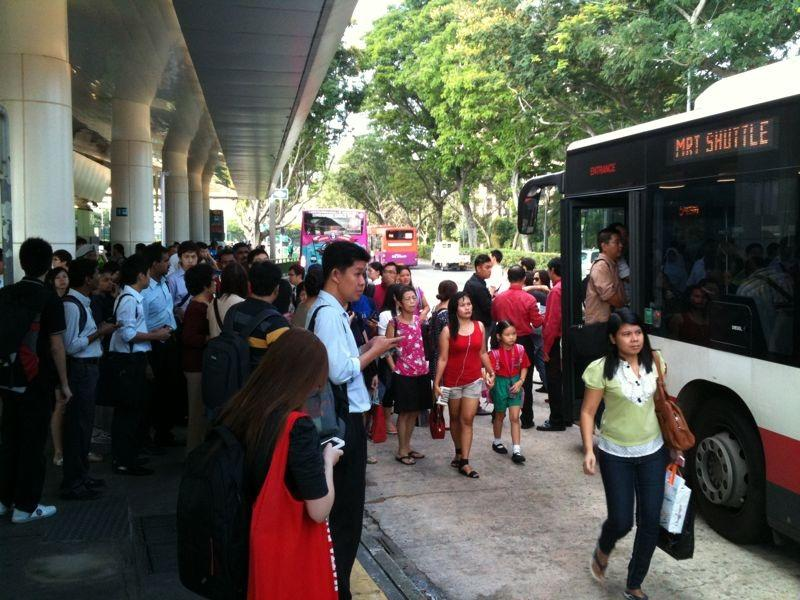 Commuters boarding a free shuttle bus outside an affected SMRT station. (Yahoo! photo)